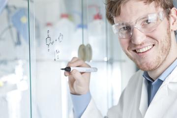 Deutschland, junger Wissenschaftler mit schriftlich chemische Gleichung auf Glas
