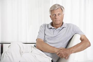 Spanien, Mallorca, Trauriger älterer Mann sitzt auf der Couch