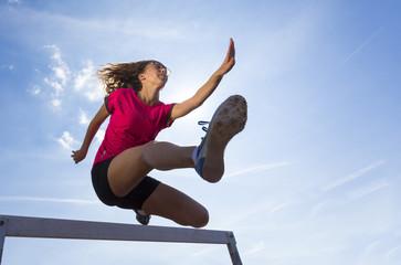 Deutschland, Junge Frau Athlet springt Hürden