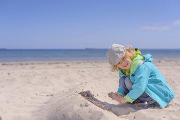 Deutschland, Mecklenburg- Vorpommern, Junge spielt mit Sand an Ostsee