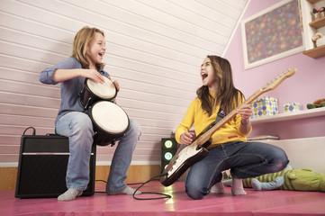 Mädchen spielen Gitarre und Schlagzeug, lachen