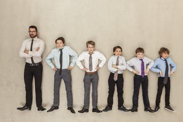 Geschäftsmann und Jungen stehen in Reihe