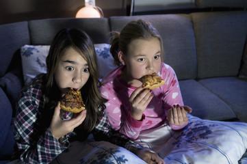 Mädchen essen Pizza beim beängstigenden Film