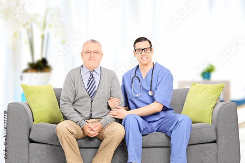 Male doctor and elderly gentleman seated on sofa
