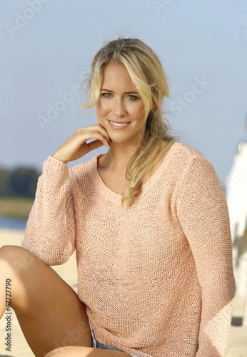 Deutschland, junge Frau sitzt am Strand