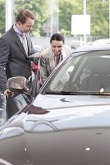 Beim Autohändler, Verkäufer, zeigt neues Auto Kunden