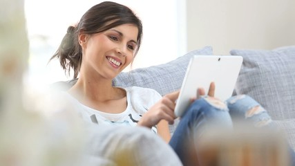 Young woman websurfing on tablet at home