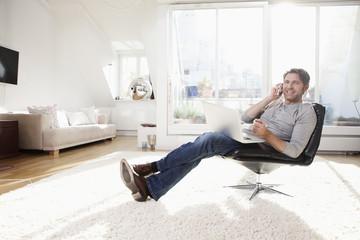 Deutschland, München, Mann mit Laptop im Wohnzimmer