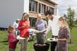 Deutschland, Nürnberg, Familie steht rund um Grill im Garten