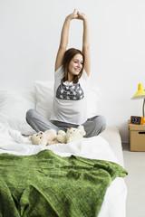 Junge Frau sitzt auf dem Bett und Stretching