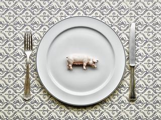 Spielzeug- Schwein auf dem Teller mit Messer und Gabel
