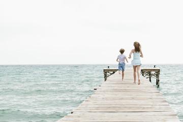 Spanien, Mädchen und Junge auf Steg läuft am Meer