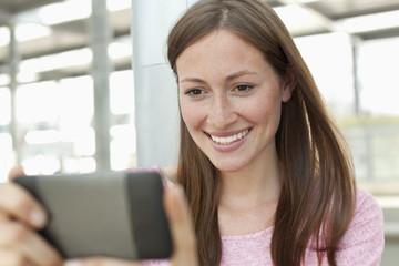 Deutschland, Düsseldorf, Junge Frau schaut Smartphone an