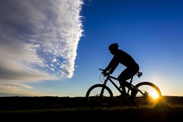 Deutschland, Winterbach, Radfahrer auf Mountainbike bei Sonnenuntergang