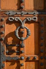 Puerta de madera y remaches de metal con llamador pintoresco