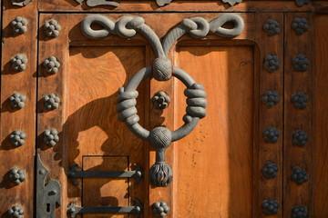 Diseño artistico de aldaba en puerta de madera con ornamento