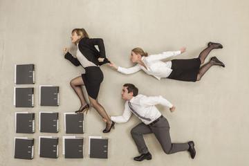 Geschäftsfrau auf Treppe von Aktenordner, während andere jagen