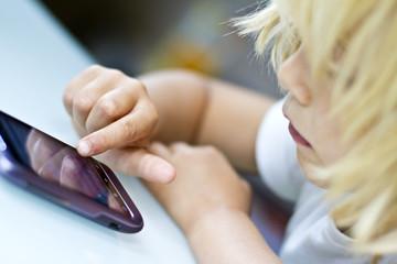 Deutschland, Kiel, Mädchen mit Smartphone spielen