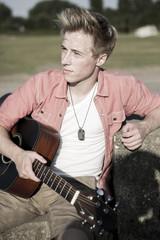 Deutschland, Junger Mann sitzt im Park mit Gitarre