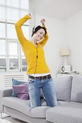 Deutschland, München, Frau Hören von Musik auf der Couch