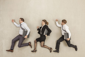 Geschäftsleute mit Aktenordner hintereinander laufen