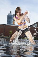 Deutschland, München, Junge Frau spritzt mit Wasser am Brunnen