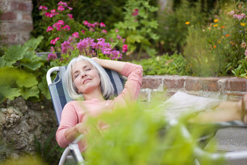 Deutschland, Bayern, Seniorin Entspannung im Garten