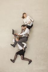 Geschäftsfrau mit Geschäftsleute mit Laptops auf den Schultern