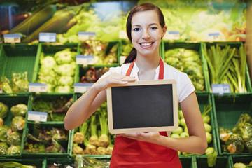 Deutschland, Köln, junge Frau mit Tafel im Supermarkt
