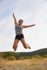 USA, Texas, Teenage Mädchen springen und hören MP3-Player