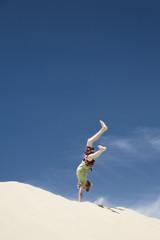 Frankreich, Junge springt auf Sanddüne