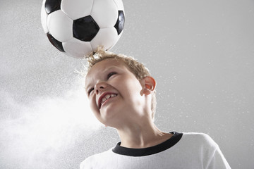 Junge im Fußball-Trikot köpfen Ball