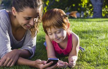 Spanien, Teenager-Mädchen und Mädchen mit Smartphone auf Gras