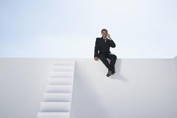 Geschäftsmann im schwarzen Anzug sitzt auf Wand und sprechen über Handy