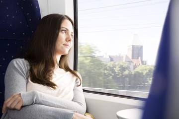 Deutschland, Brandenburg, Frau mittleren Alters, durch Fenster im Zug schauen
