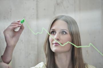 Deutschland, Köln, Geschäftsfrau Zeichnung Diagramm auf Glas, Wegschauen
