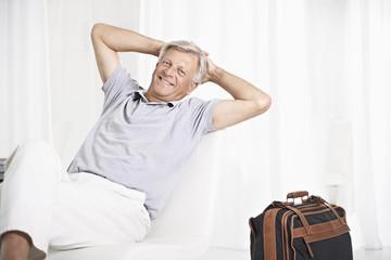Spanien, Mann wartet in der Lobby mit Koffer