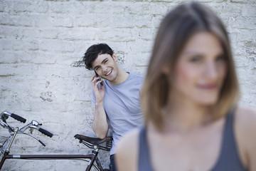 Deutschland, Köln, junge Frau Wegschauen beim Mann sprechen auf Handy im Hintergrund