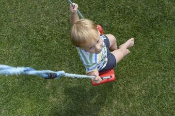 Kleiner Junge auf einer Schaukel im Garten sitzen
