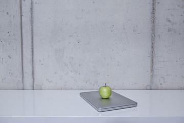 Deutschland, Köln, Grüner Apfel mit Laptop auf dem Regal