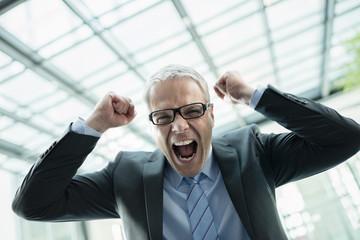 Deutschland, Stuttgart, Geschäftsmann lachend in Bürogebäude
