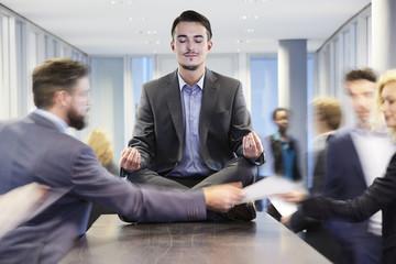 Deutschland, Geschäftsmann meditiert auf dem Schreibtisch