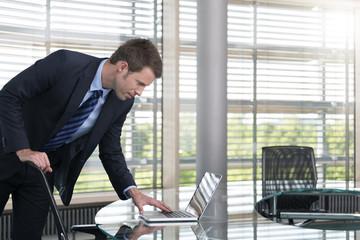 Deutschland, Hannover, Geschäftsmann mit Laptop am Konferenztisch
