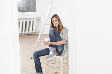 Frau mit Tasse sitzt auf dem Stuhl