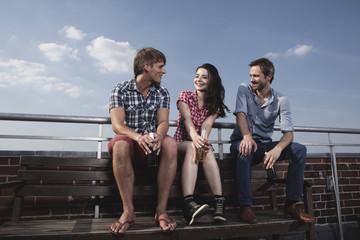 Deutschland, Berlin, Mann und Frau sitzen auf der Dachterrasse