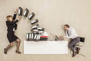 Kaufmann arbeitet an Büro-Schreibtisch, während Geschäftsfrau bietet Stapel von Aktenordner
