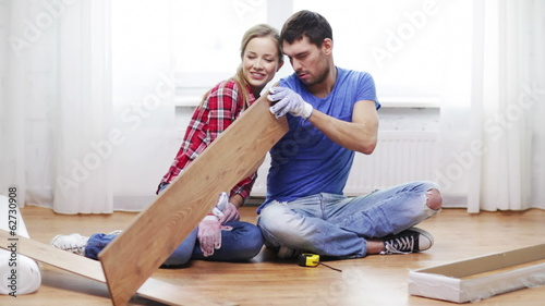 couple taking out wood flooring from package