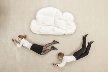 Geschäftsfrauen, die Handy und unter Wolke Form Kissen fliegen