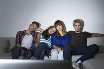 Deutschland, Berlin, Gruppe junge Leute sitzen auf der Couch vor der Leinwand