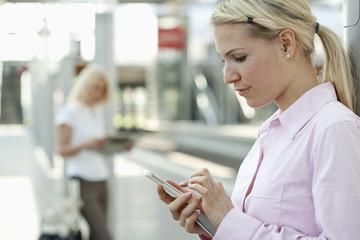 Deutschland, Düsseldorf, Frau mit Smartphone, Business-Frau liest Zeitung im Hintergrund